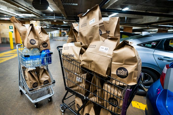 Online grocery orders await delivery at a Whole Foods in Washington, DC. More people are turning to delivery services as the coronavirus outbreak continues.