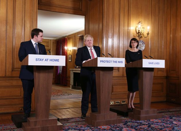 Britain's Prime Minister Boris Johnson, is joined by Housing, Communities and Local Government Secretary Robert Jenrick, left, and Deputy Chief Medical Officer Jenny Harries, right, during a daily COVID 19 coronavirus press briefing to announce new measures to limit the spread of the virus, at Downing Street in London Sunday March 22, 2020.  For some people the COVID-19 coronavirus causes mild or moderate symptoms, but for some it can cause severe illness including pneumonia. (Ian Vogler / Pool via AP)