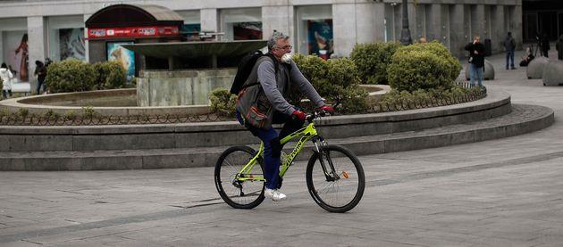 Un hombre circula en bicicleta por la Puerta del Sol de