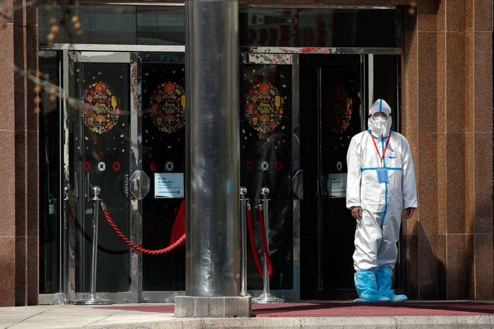 A worker wearing a protective suit stands outside a hotel converted into a quarantine location for travelers from overseas in