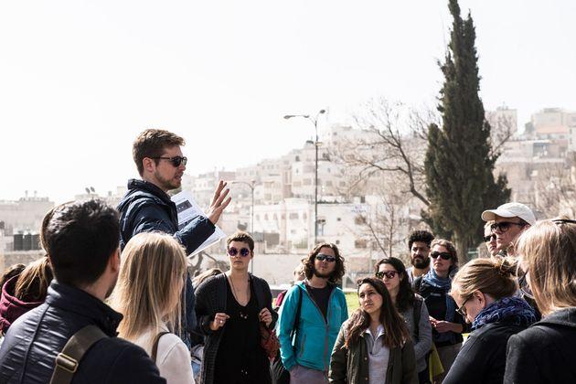 ツアー参加者に自身の経験を語るアブネルさん。ヘブライ語で行うツアーには、ユダヤ系住民も参加するという。