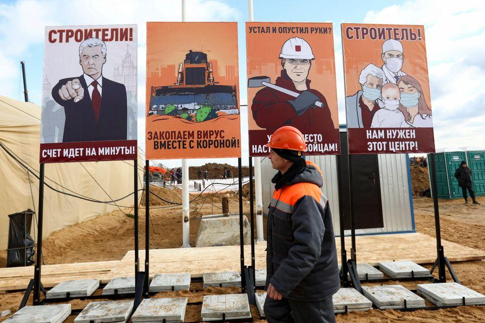 Πόστερ σε στυλ σοβιετικής προπαγάνδας καλούν τους εργάτες να δουλέψουν ακόμα πιο γρήγορα, για να χτίσουν ένα νέο νοσοκομείο στα περίχωρα της Μόσχας.