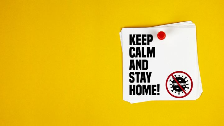 Keep Calm And Stay Home motivation letter written on post-it paper against Coronavirus