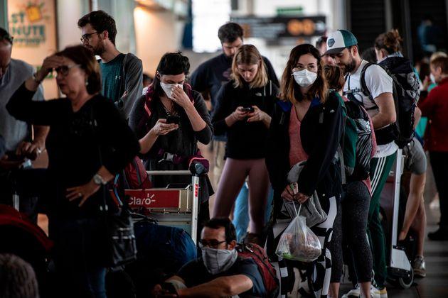 Des passagers portent des masques pour prévenir la propagation du coronavirus, COVID-19, alors...