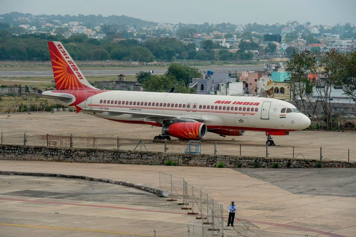 A security personnel stands guard near an Air India Airbus A-320 displayed at Begumpet Airport in Hyderabad on March 14, 2020. (Photo by NOAH SEELAM / AFP) (Photo by NOAH SEELAM/AFP via Getty Images)