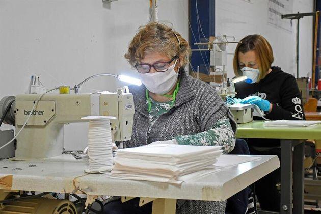 Varias mujeres fabrican mascarillas mientras colaboran de forma altruista con la empresa segoviana Mundo