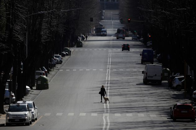 A woman walks her dog in the EUR neighbourhood in Rome, Monday, March 23,