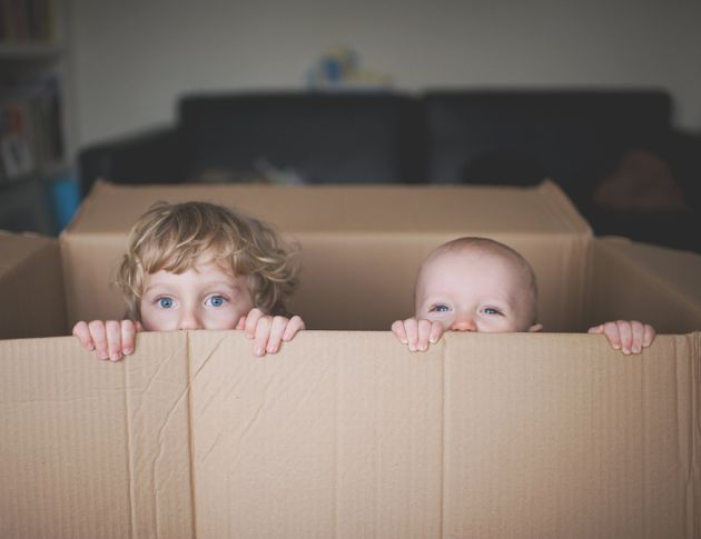 Small kid and baby playing in and looking out of a cardboard