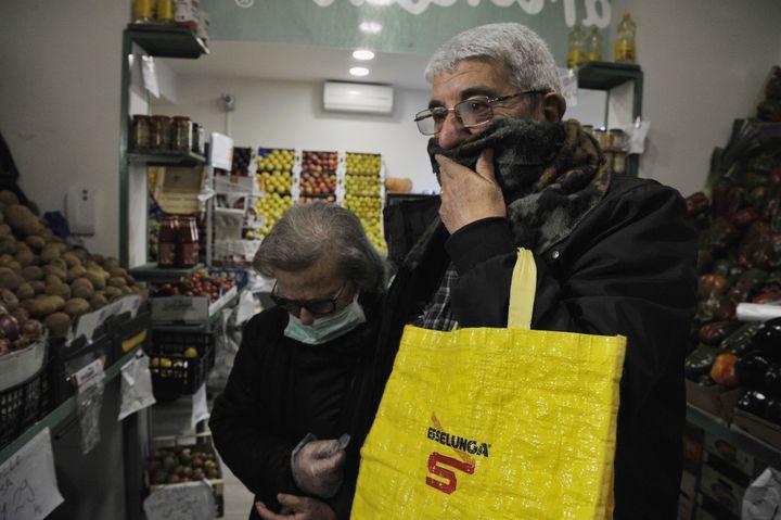 Un hombre se tapa la boca con una bufanda en un supermercado italiano.