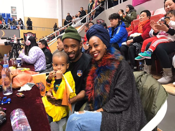 Imani Basheer attends a football game in Wuhan, China, with her husband and son. The family was forced to sell their belongin