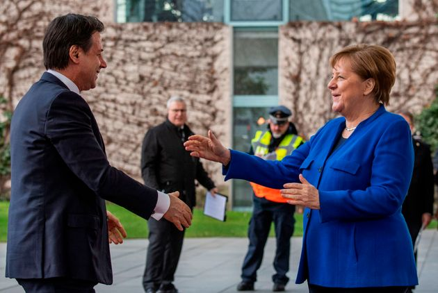 German Chancellor Angela Merkel (C) greets Italian Prime Minister Giuseppe Conte upon his arrival to...