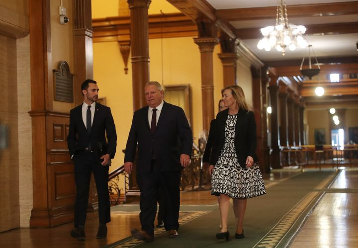 Ontario Premier Doug Ford walks through Queen's Park with cabinet ministers before an announcement on March 20, 2020.