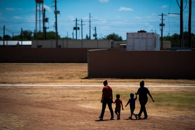 Immigrant women and children walk across a field as Immigration and Customs Enforcement and Enforcement...