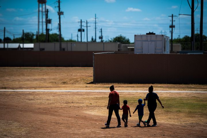 Immigrant women and children walk across a field as Immigration and Customs Enforcement and Enforcement and Removal Operation