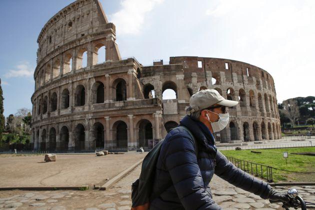 Un homme avec son masque passe devant le Colisée à Rome le 15 mars 2020 (photo