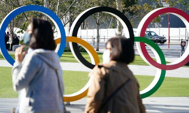 オリンピックシンボル前を歩くマスク姿の人。