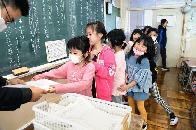修了式を終え、担任の先生から通知表を受け取る児童たち=2020年3月24日午前8時55分、東京都国立市の国立第四小学校、伊藤進之介撮影