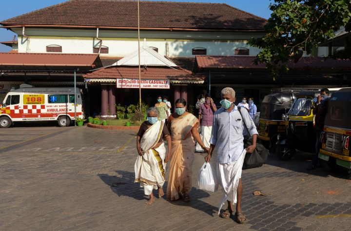 Indians wearing surgical masks walk out of the government general hospital where the student who had been in Wuhan was kept in isolation in Thrissur, Kerala, Jan. 30, 2020.