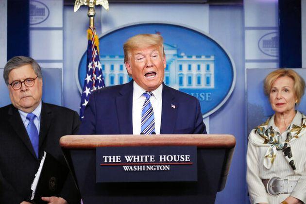 23日、ホワイトハウスの会見で話すトランプ米大統領(中央)=AP