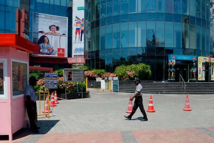 Security personnel stand at the entrance of a shopping mall closed in Chennai on March 17, 2020.