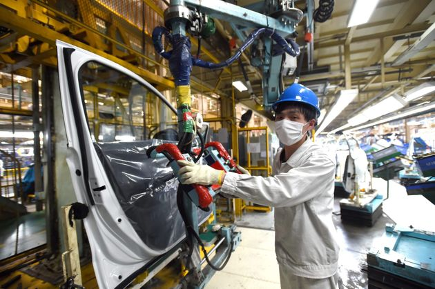 A masked man works on an assembly line on March 16 at a Dongfeng Honda plant in Wuhan, China. This is...