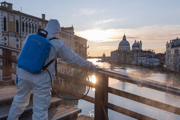Un operario desinfecta el puente de la Accademia en Venecia