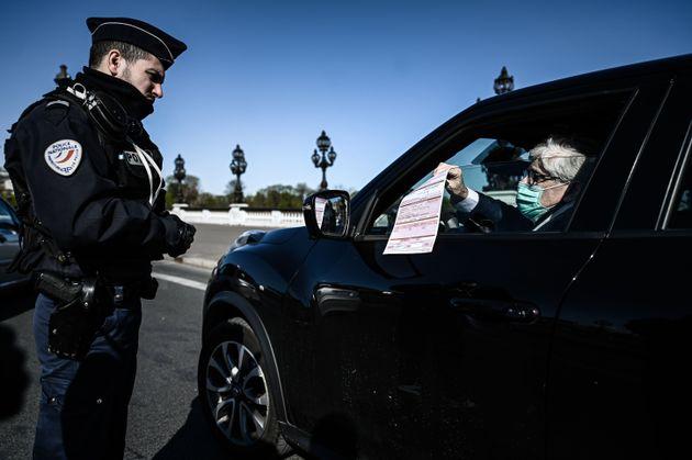 Un membre de la police nationale contrôlant un homme en voiture à Paris pendant le confinement,...