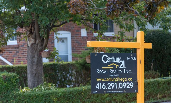 In this file photo, a Century 21 for-sale sign is seen on a lawn in Toronto, Oct. 12. 2016. The Ontario Real Estate Association is calling for an end to person-to-person contact in home sales.