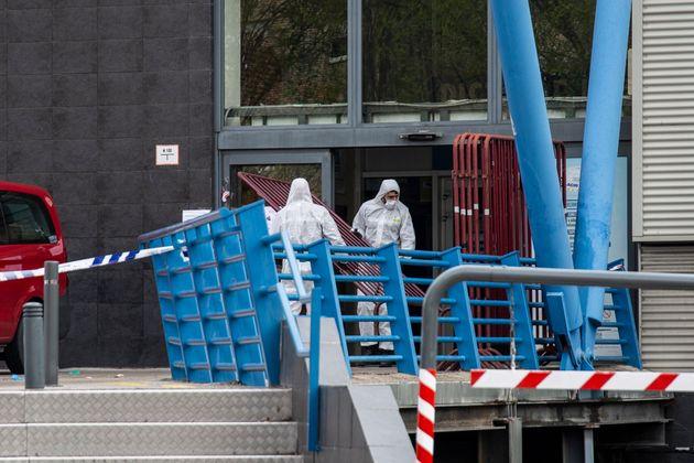 遺体安置所じ使われているアイススケート場で、防護服をきて柵を設置する緊急事態部隊