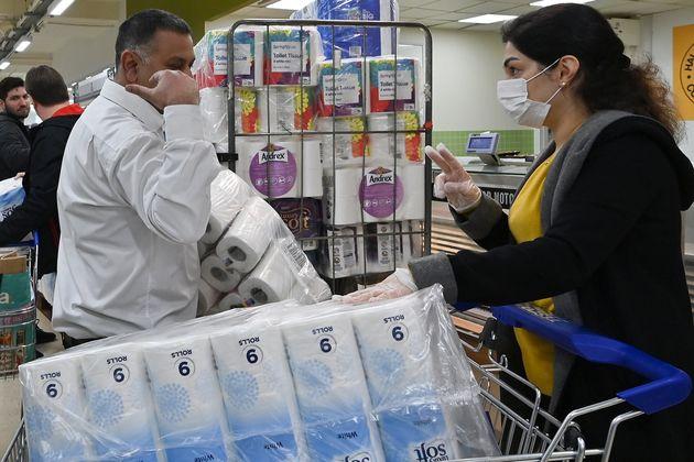 スーパーでトイレットペーパーの購入数の制限を確認する女性 2020年3月14日・ロンドン