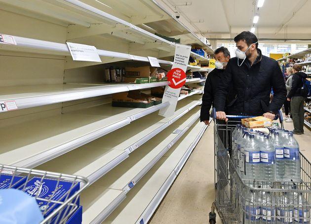 ロンドンのスーパーで空っぽの棚を眺める客 2020年3月14日・ロンドン