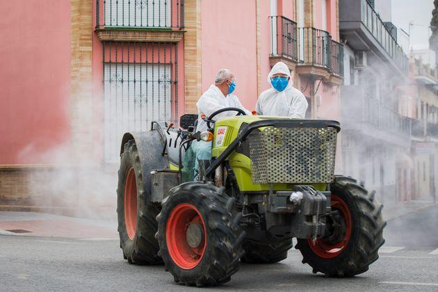 방역 작업을 돕고 나선 농민들이 트랙터 등을 이용해 마을을 소독하고 있다. 세비야, 스페인. 2020년