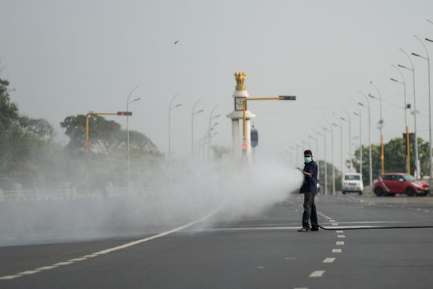 A health worker sprays disinfectant on a deserted road during the one-day Janata (civil) curfew imposed...