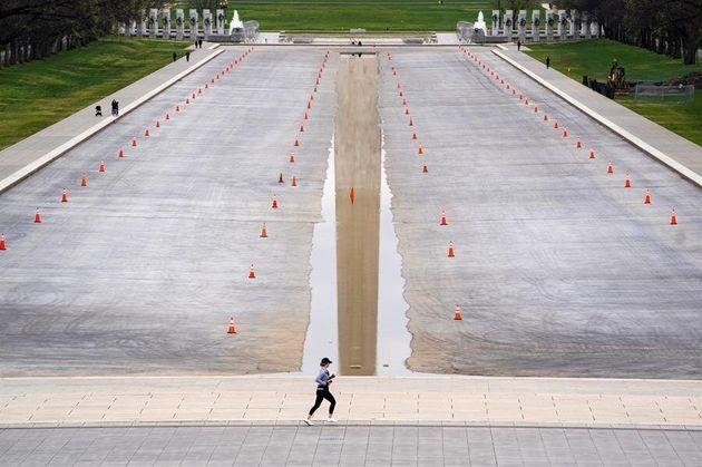 Una mujer hace ejercicio este martes en el estanque reflectante del monumento a