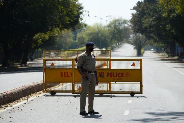 인도 정부가 전 국민을 대상으로 외출금지령을 내린 가운데 경찰관이 도로 위에 설치된 검문소를 지키고 있다. 뉴델리. 2020년