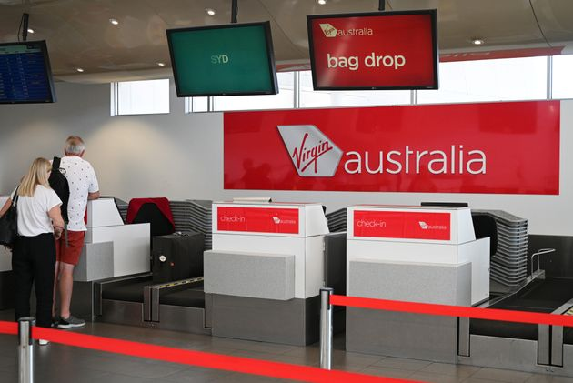 Travelers stand at a Virgin Australia Airlines counter at Kingsford Smith International Airport, following...