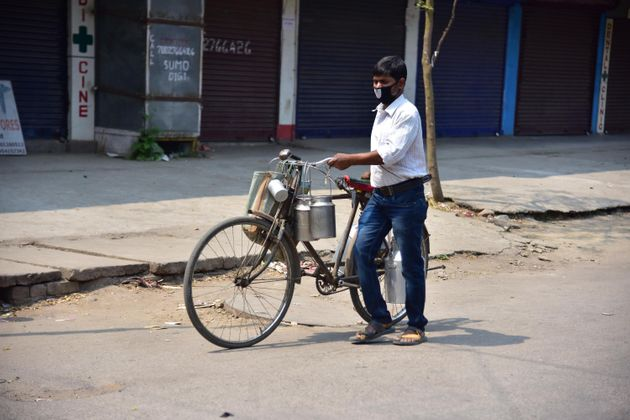 A milkman pushes a bicycle during a nationwide lockdown in the wake of coronavirus pandemic, in Nagaon...