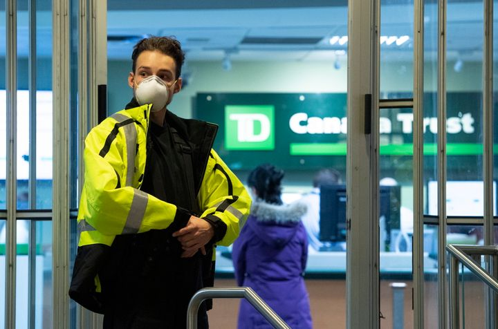 A security guard at a TD Bank wears a mask as he limits the number of clients in the bank to help prevent the spread of COVID-19 in Ottawa on March 24, 2020.