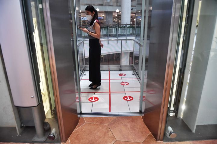 A woman stands in an elevator with markers on the floor for social distancing measures in a shopping mall in Bangkok on March 20.