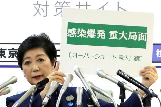 Governadora de Tóquio, Yuriko Koike, segura placa que traz em japonês a expressão...