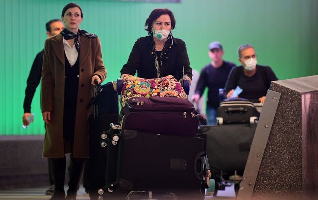 International travelers, some wearing face masks, arrive at Los Angeles International Airport on March...