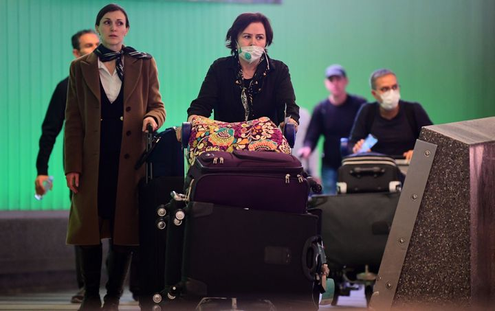 International travelers, some wearing face masks, arrive at Los Angeles International Airport on March 12, 2020, one day befo
