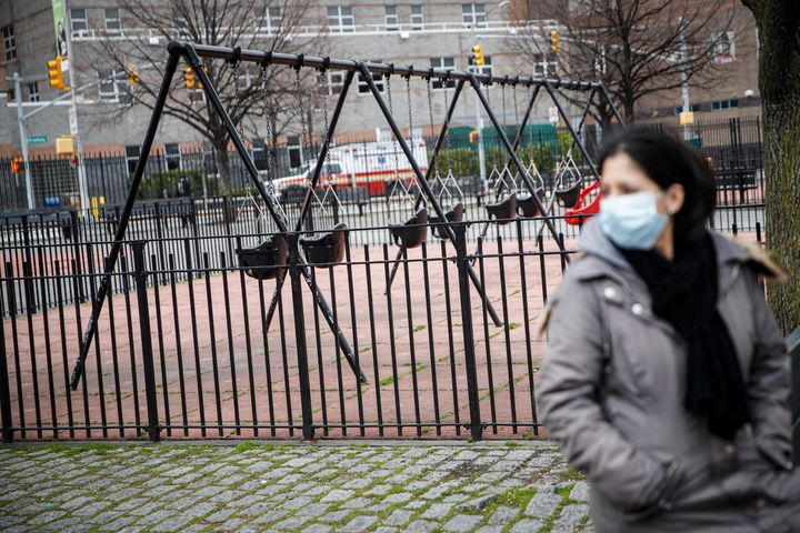 A woman wearing personal protective equipment sits alone alongside empty swings to maintain social distancing at a playground