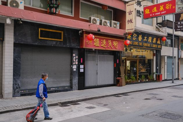 HONG KONG, CHINA - MARCH 26: A man walks past some empty stores during a coronavirus (COVID-19) outbreak...