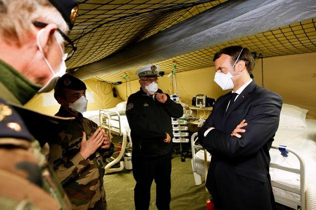 Emmanuel Macron, ici lors de la visite de l'hôpital militaire de campagne à l'extérieur...