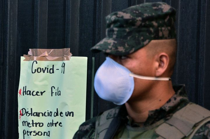 A soldier wearing a face mask stands next to a sign about preventive measures to stop the spread of COVID-19 in Honduras. The government declared a national curfew on March 16, 2020.