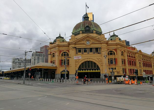 Mobile photo shows few people standing in front of the Flinders Street Station in Melbourne, Australia,...