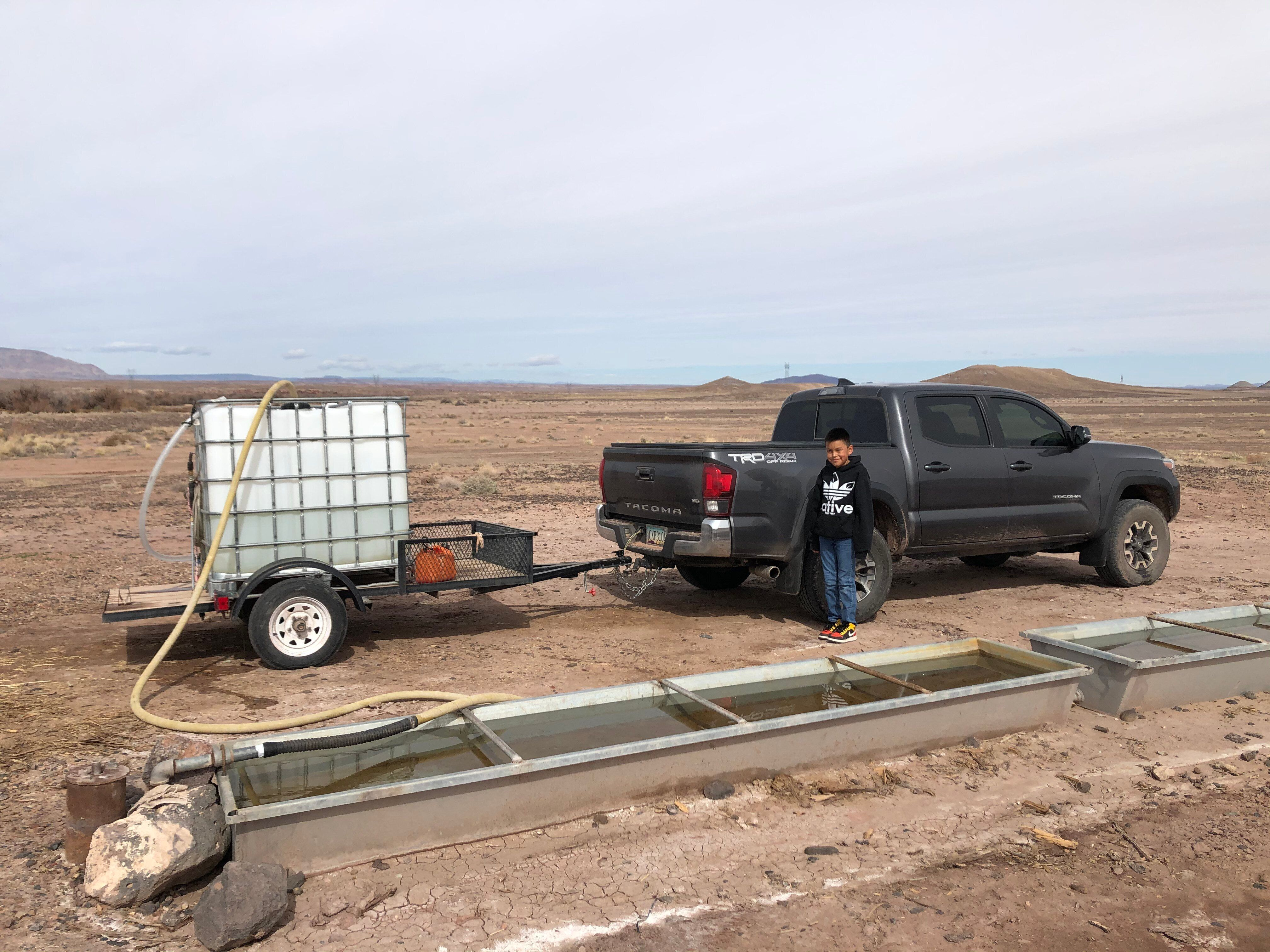 Shanna Yazzie's 10-year-old son stands by the family's truck as water for their use is pumped from a nearby windmill.