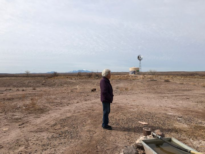 Shanna Yazzie's 79-year-old mother stands by the nearby windmill pump the family relies on for bathing water.