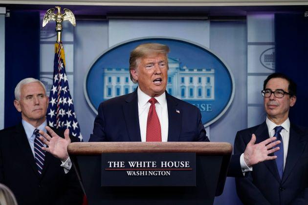 마이크 펜스 부통령(왼쪽)과 스티므 므누신 재무장관(오른쪽)이 지켜보는 가운데 도널드 트럼프 대통령이 백악관 코로나19 브리핑에서 발언하고 있다. 2020년